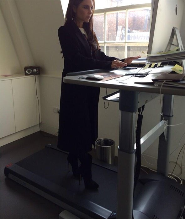 Victoria Beckham trying out a treadmill desk while wearing high-heeled booties in a snap she shared on Twitter on March 12, 2014