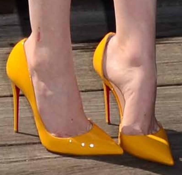 Emma Stone wearing bright yellow patent pumps from Christian Louboutin