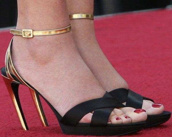 Kate Winslet's feet inblack-and-gold ankle-strap sandals
