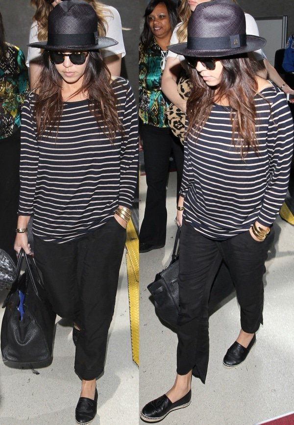 Kourtney Kardashian in a long-sleeved striped shirt, black pants