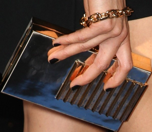 Maggie Q toting a gold clutch