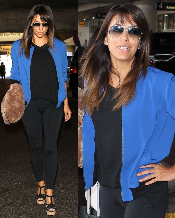Eva Longoria wearing a black outfit with a blue jacket at LAX