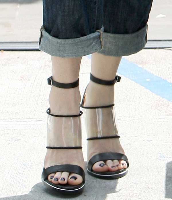 Gwen Stefani wearing sandals featuring leather front straps, buckled ankle straps, clear vinyl midstraps, and four inches of slender and translucent wedge heels