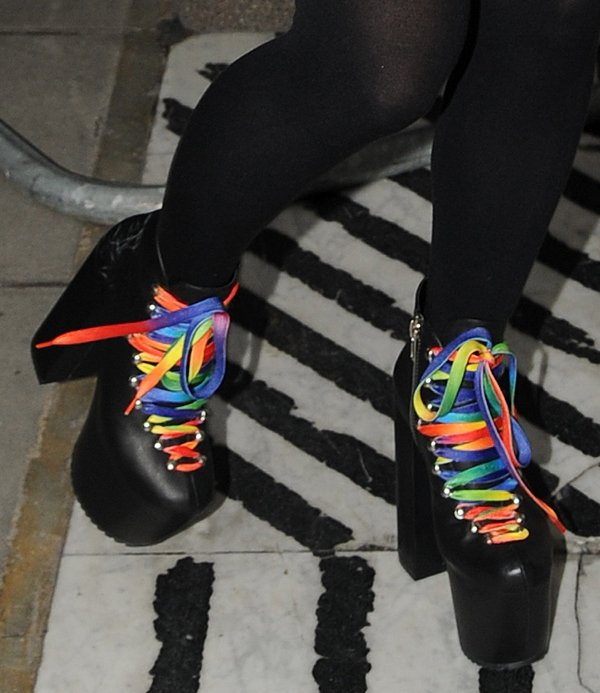 Lily Allen in black boots withstriking rainbow laces