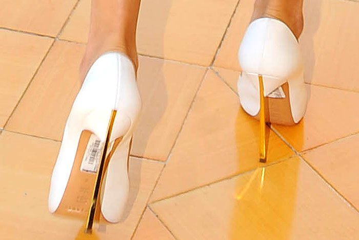 Closeup of Selena Gomez's white Casadei gold-blade-heel pumps