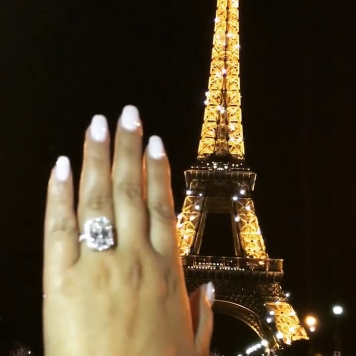Adrienne Bailon's engagement ring features colorless an 8-carat emerald-cut diamond embraced by a halo of French-pave set diamonds set in platinum