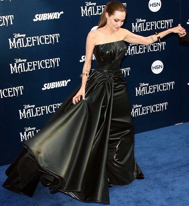 Angelina Jolie adjusting the layers of leather on her Versace strapless gown