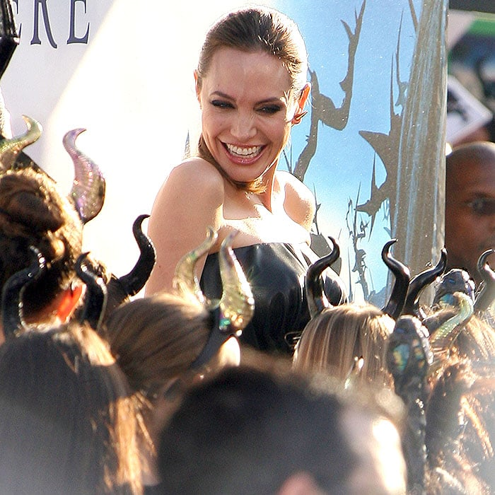 Angelina Jolie surrounded by little girls sporting Maleficentheadbands at theMaleficent world premiere