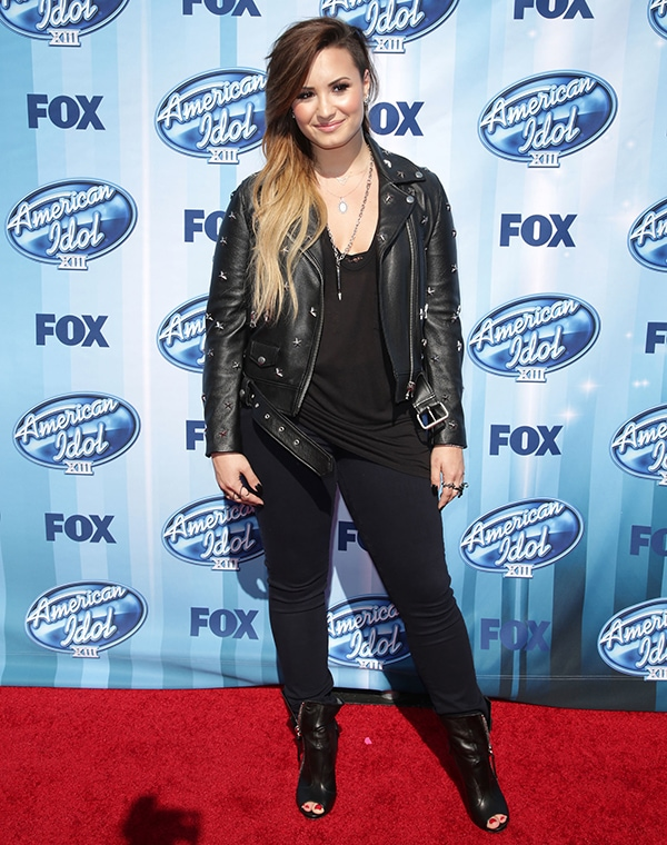 Demi Lovato wearing a simple black tank top, skinny jeans, and a studded leather jacket