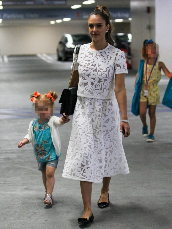 Jessica Alba wearing a white floral dress and flat shoes and holding hands with daughter Haven Warren as she takes her children to the Hammer Museum of Art in Los Angeles on May 18, 2014