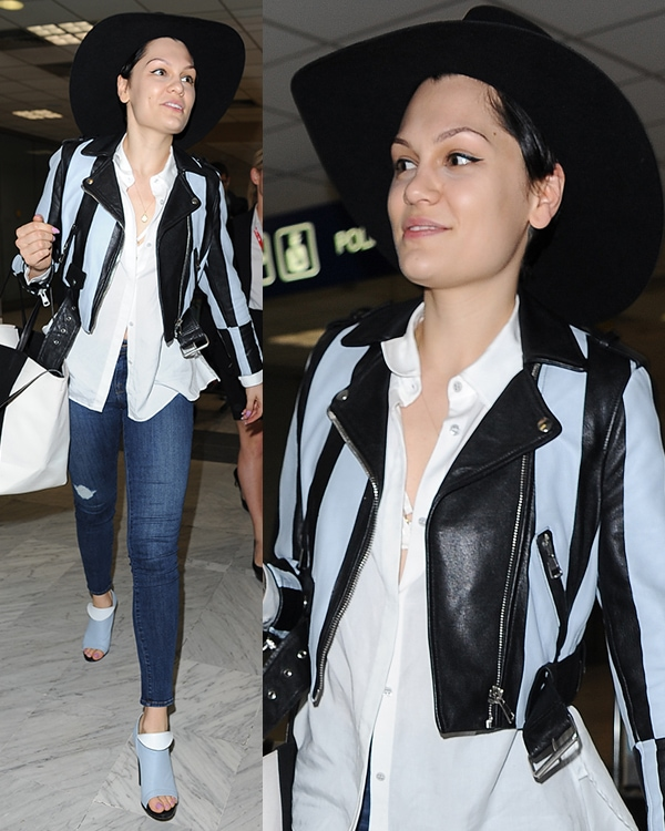 Jessie J in a white top, a pair of denims, a black wide-brimmed hat, a blue-and-black leather jacket, and matching peep-toe booties with fold-over detail by Balenciaga