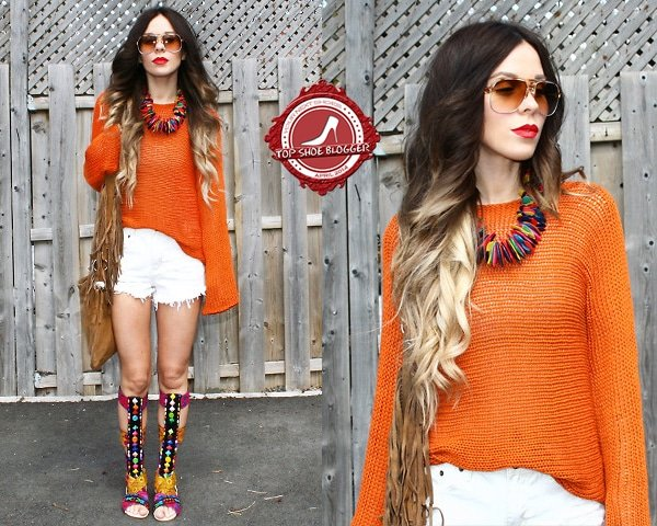 Katie flaunts her legs in an orange knit top and white frayed shorts