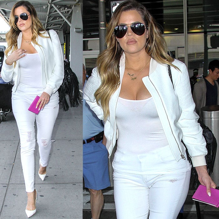 Khloe Kardashian in a white tank, white leather jacket, white jeans, and white snake pumps