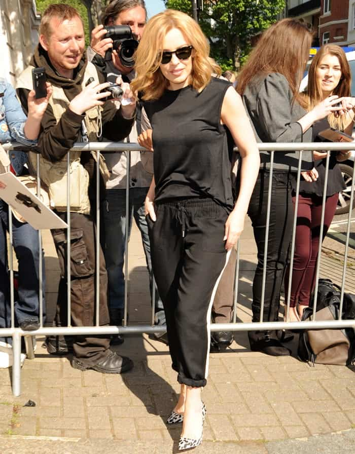 Kylie Minogue in an all-black outfit accessorized with spotted pumps
