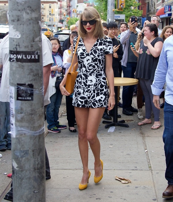 Taylor Swift accessorized with jewelry by Red C Jewels and a streamlined satchel by Bhailiu