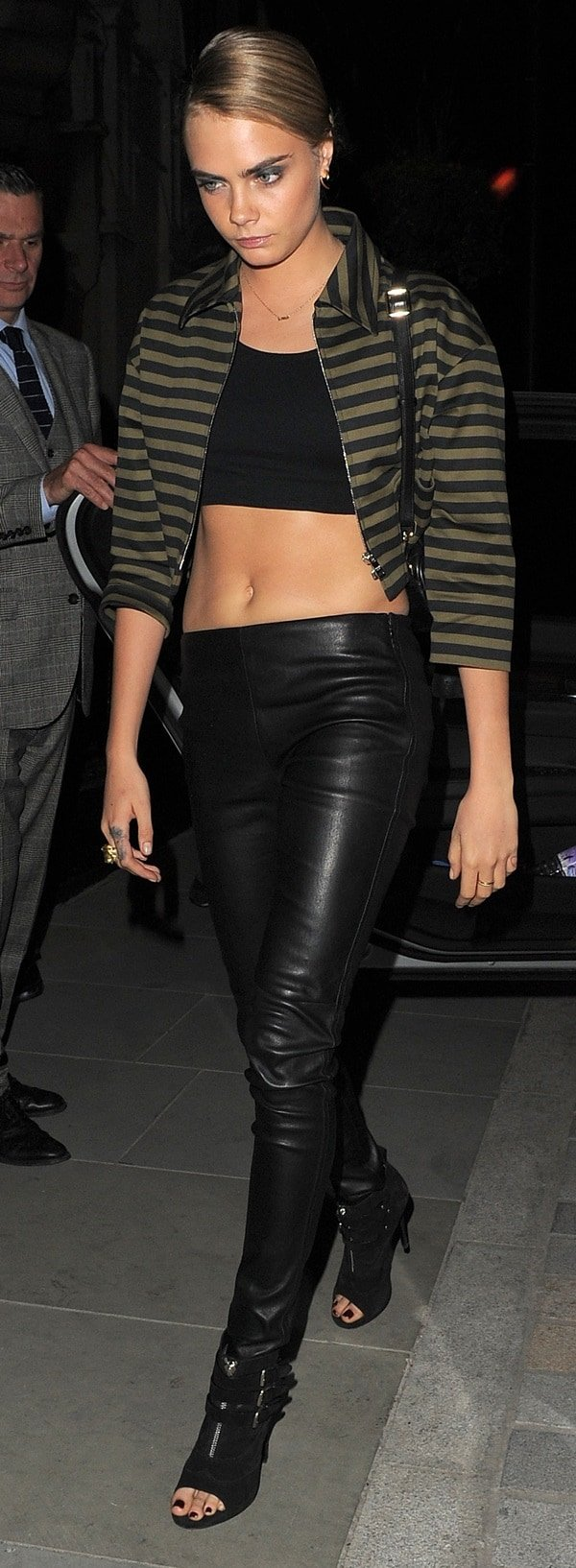 Cara Delevingnein black leather pants paired with a crop top layered beneath a striped blazer