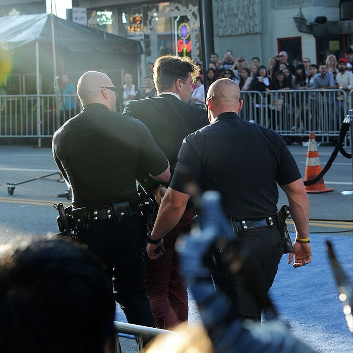 Police arresting andleading awayVitalii Sediuk, the man who jumped the barriers and tried to make contact with Brad Pitt's face as the actorwalked down the red carpet