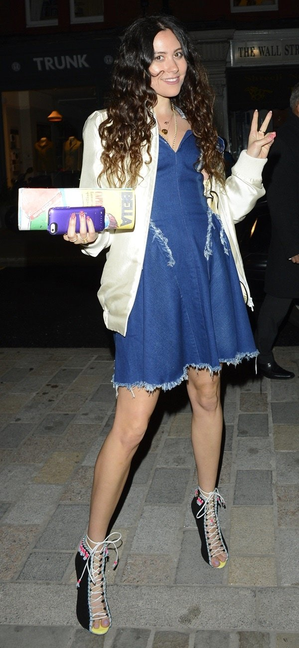 Eliza Doolittle wearing a frayed denim dress, a silk jacket, and unidentified lace-up heels with multicolored beads