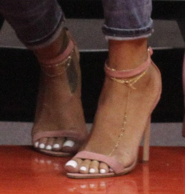 Rihanna displays her ankle chain and tattoo