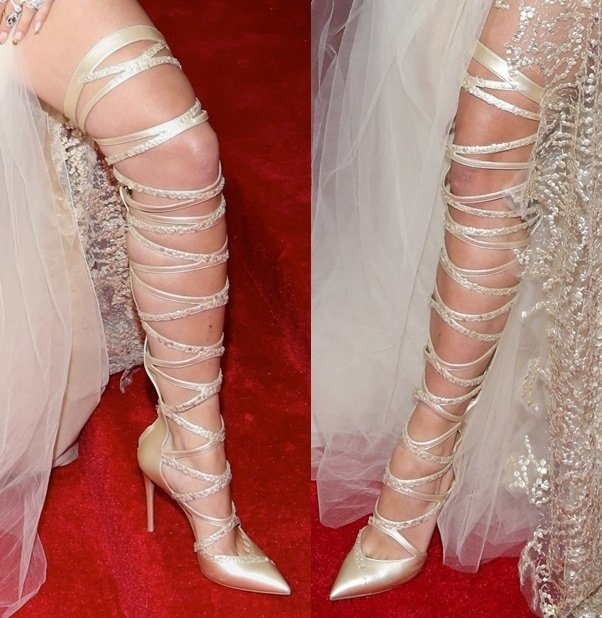 Rita Ora wearing striking strappy thigh-high pumps at the 2014 Met Gala held at the Metropolitan Museum of Art in New York City on May 5, 2014
