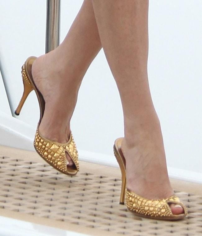 Sharon Stone wearing gold studded mules