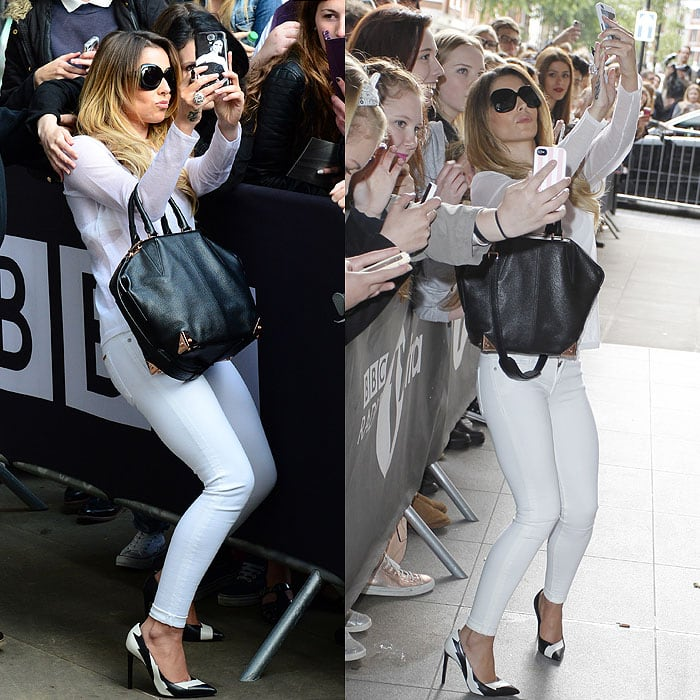 Cheryl Cole crouching to take pictures with fans
