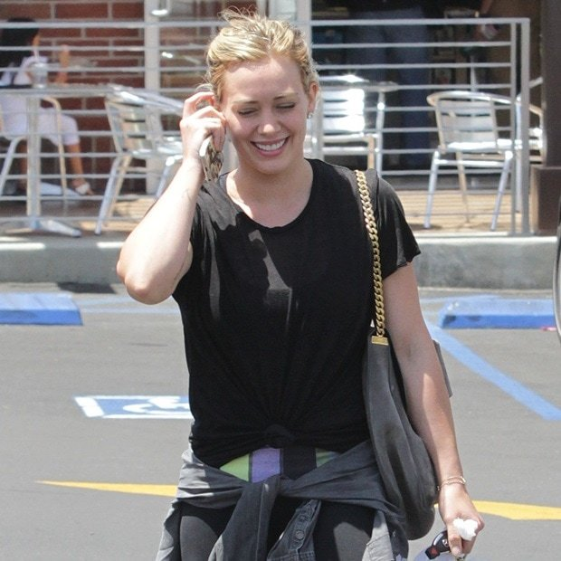 Hilary Duff spotted wearing black sportswear with a gray sweater tied around her waist in Beverly Hills on June 15, 2014