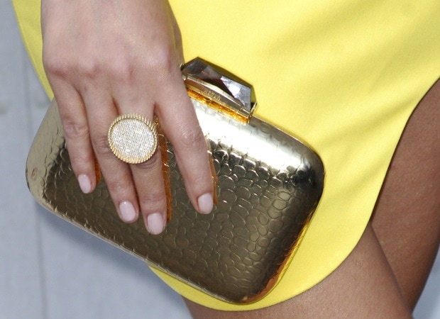 Chrissy toting a gold croc-embossed Morley box clutch bag by Kotur