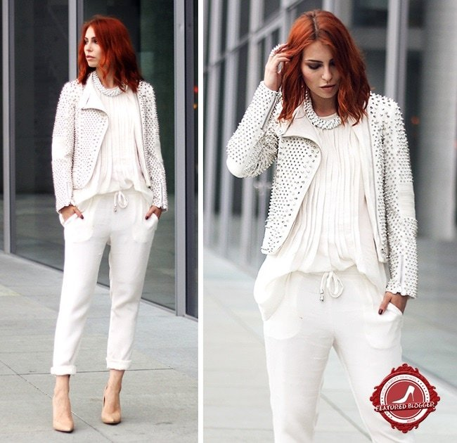 Fashion blogger Masha Sedgwick scoring a perfect hit with an all-white outfit detailed with a studded jacket, a gorgeous necklace, and some classic nude pumps