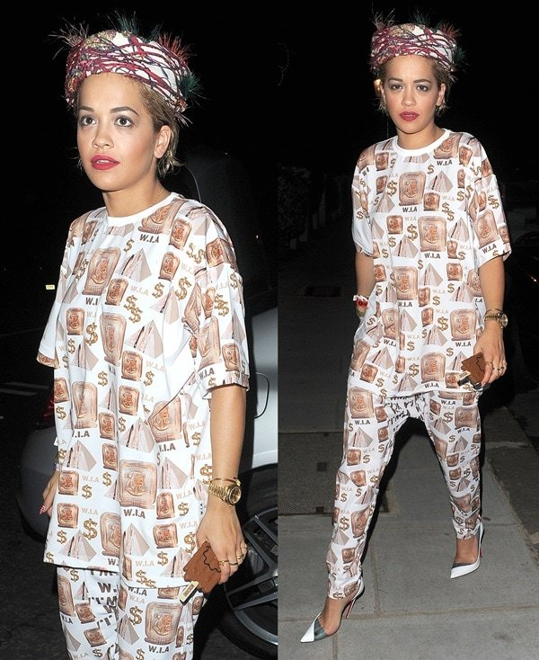 Rita Orawearing a baggy W.I.A. Collections outfit that features an Egyptian-themed print made up of pyramids, hieroglyphs, and dollar signs
