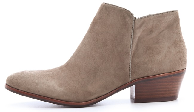 These suede booties feature tonal grosgrain piping at the notched top line and side seams