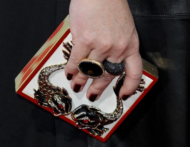 Melissa McCarthy showing off a boxy embellished clutch and stacks of rings