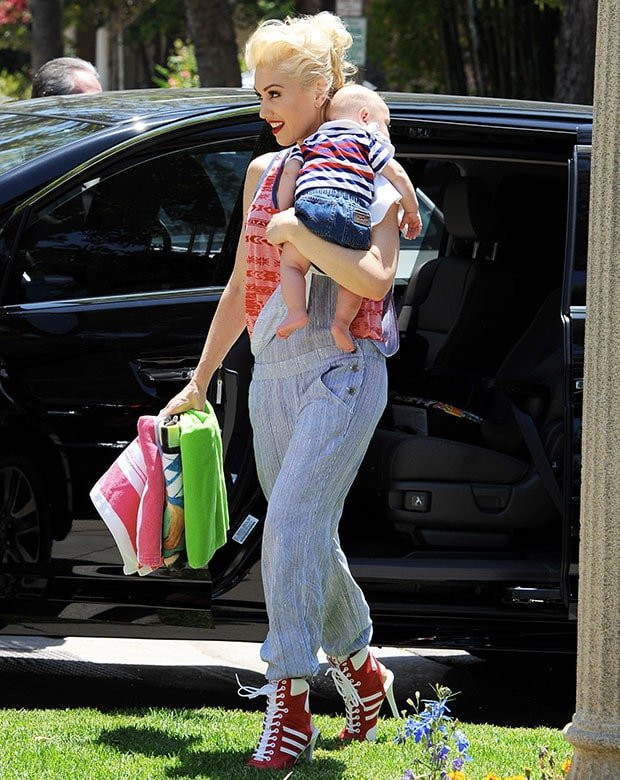 Gwen Stefani in a patterned and blue-trimmed red tank top paired with muted blue overalls