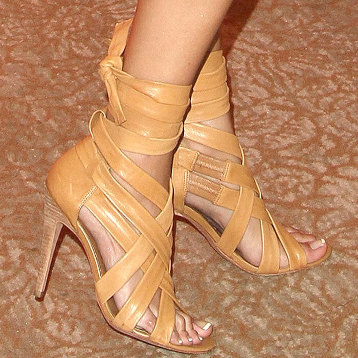 Italia Ricci wearing tan strappy sandals