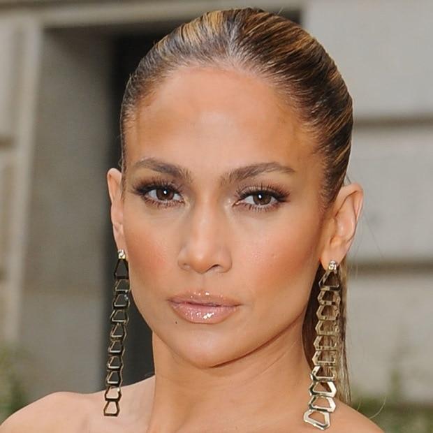 Jennifer Lopez showing off her dangling gold earrings