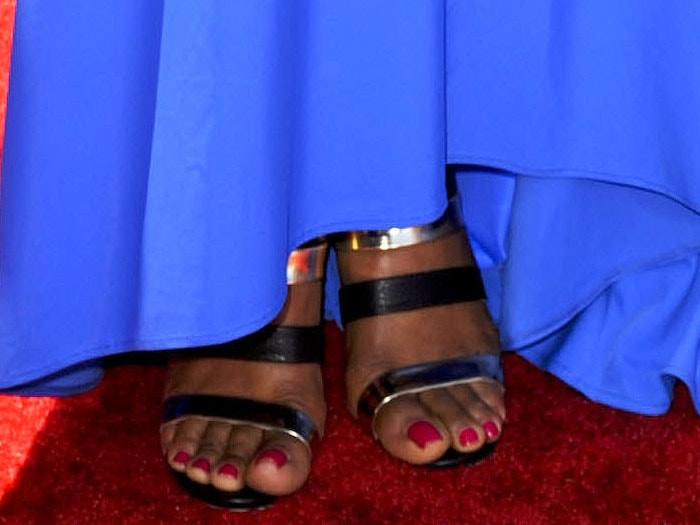 Laila Ali wearing gold and black strap sandals
