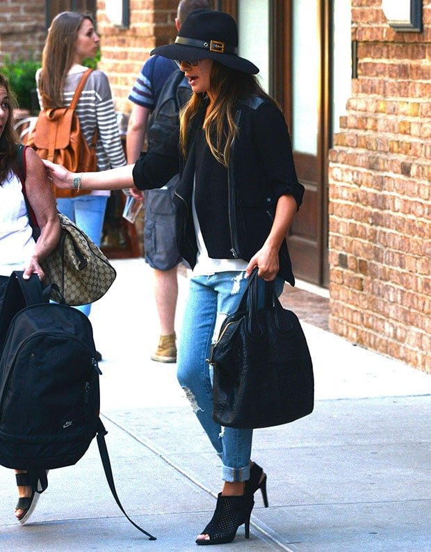Lea Michele styled the outfit with a black jacket, a black Givenchy bag, a wide-brim black fedora, and tinted aviators