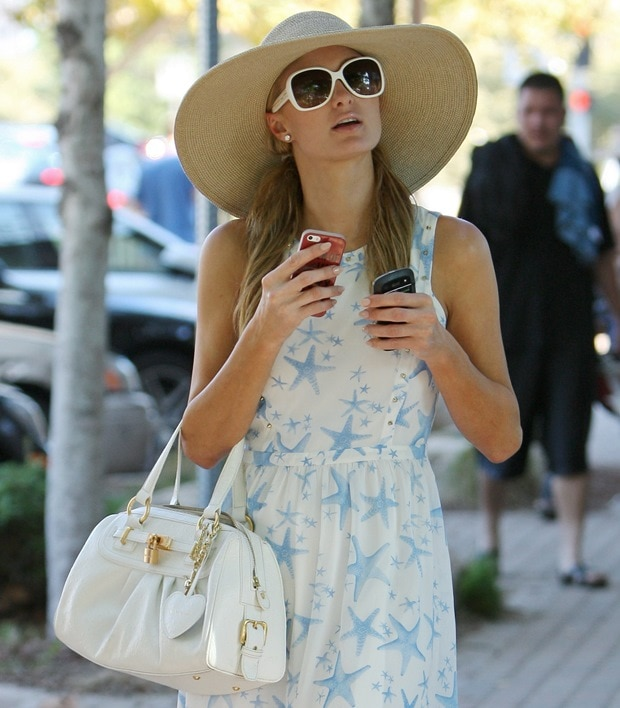 Paris Hilton shows off her white handbag and Prada sunglasses