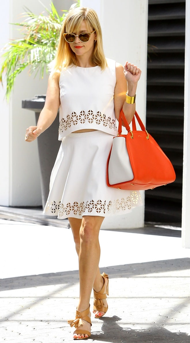 Reese Witherspoon wearing a sleeveless white cropped top and a matching high-waist skater skirt