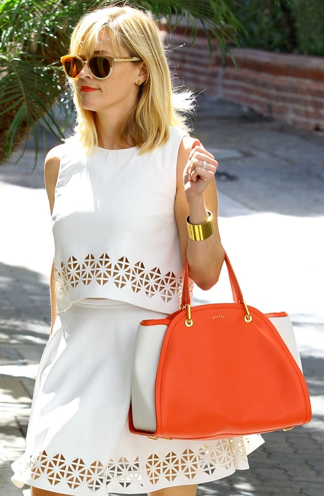 Reese Witherspoon complemented the outfit with cat-eye sunnies, red-orange lipstick, and a structured handbag painted in the same tangerine hue
