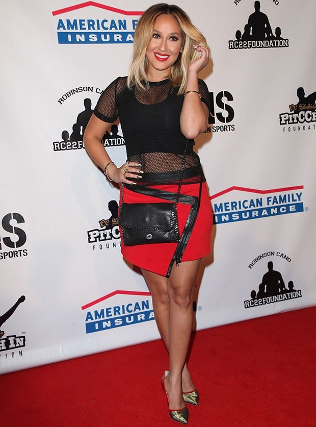 Adrienne Bailon wearing a black Helmut Lang mesh top and a red Ohne Titel jersey skirt with leather trims and an asymmetrical zipper in front