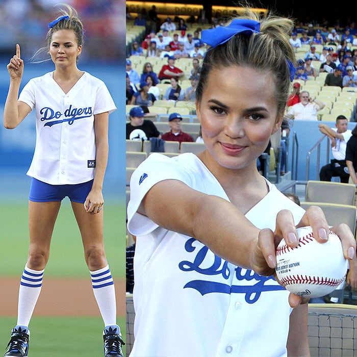 Chrissy Teigen at the pitcher's mound and holding up the ball she used for the ceremonial first pitch