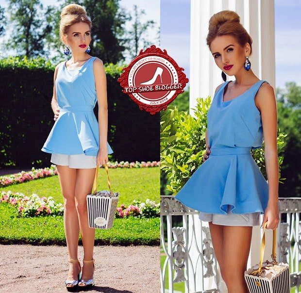 Darya in a chic blue peplum top with gray shorts