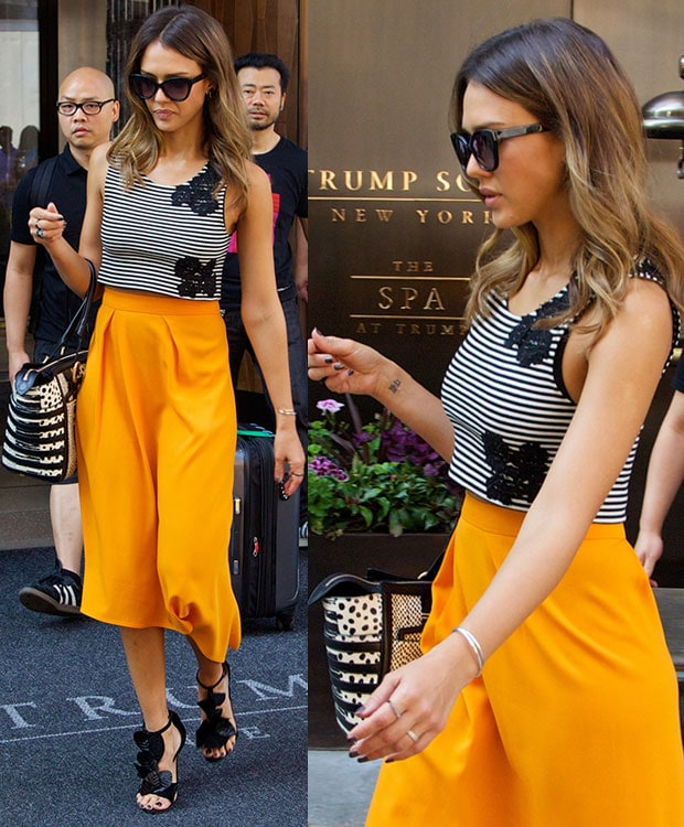 Jessica Alba wearing an orange high-waist Osman asymmetrical midi skirt and a black-and-white Houghton striped crop top