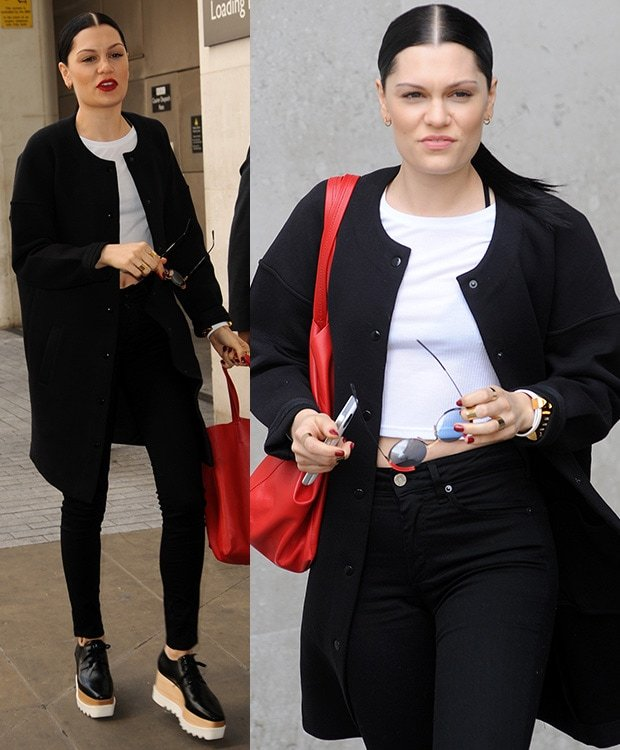 Jessie J wearing a white cropped top, a pair of high-waisted black pants, and a black coat