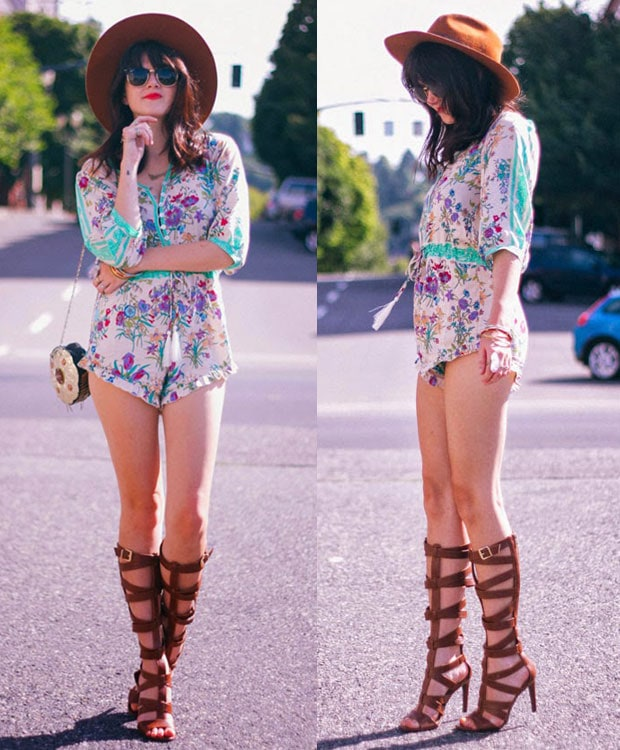Kacie Cone in a floral romper, a hat, and knee-high gladiator sandals