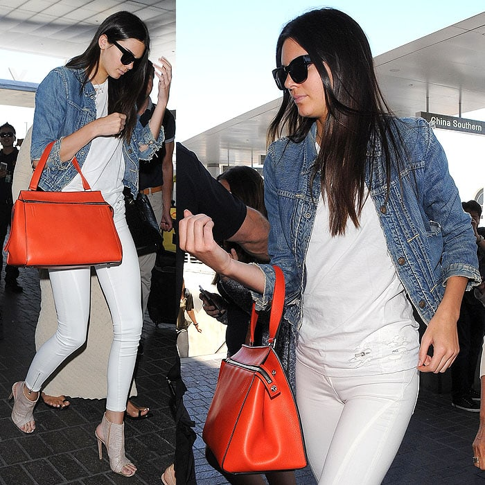 Kendall Jenner sporting a destroyed denim jacket and white tee with white jeans, black sunglasses, an orange Celine Edge handbag, and open-toe booties