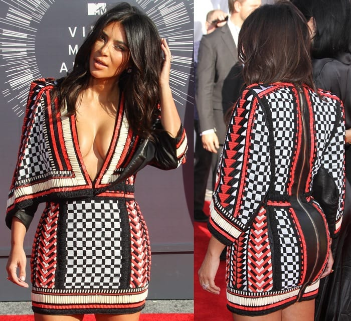 Kim Kardashian flaunted her cleavage in a heavily beaded plunging mini dress from the Balmain Resort 2015 collection featuring a cape-like shape