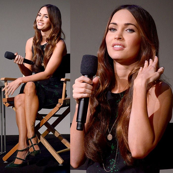 Megan Fox flashing the audience a smile and giving her hair a flirty flip