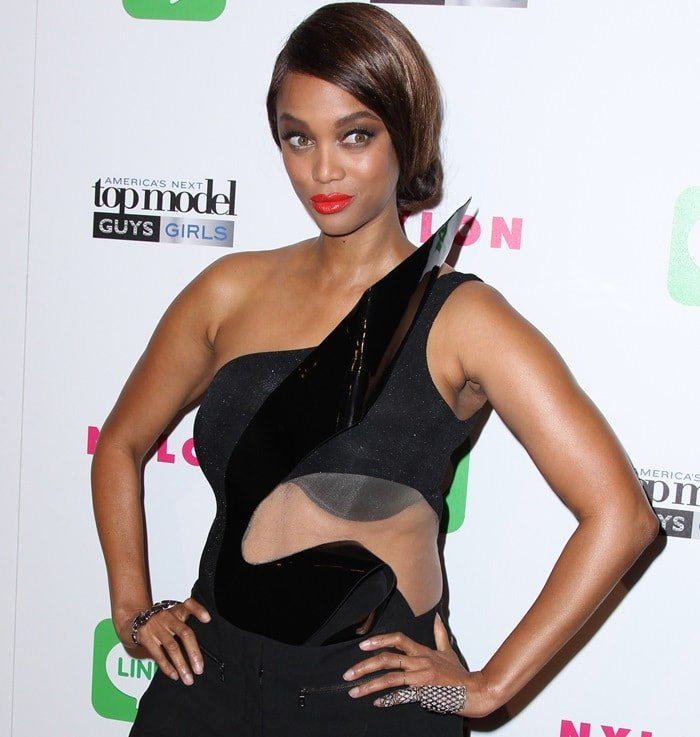 Tyra Banks disappointed in a heinous all-black outfit by Alon Livné featuring an oddly shaped sheer panel on the waist